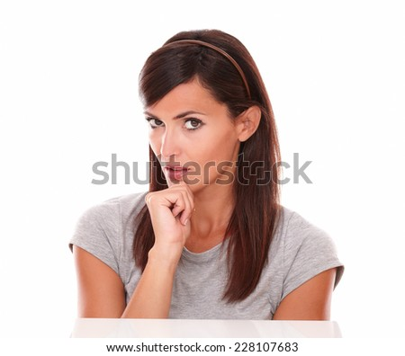 Portrait of attractive female on grey t-shirt wondering with her hand on chin while looking at you on isolated studio - stock photo