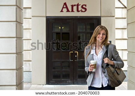 Portrait of attractive female student outside campus building - stock photo