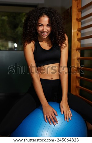 Portrait of attractive fit girl sitting on balance ball looking to the camera, pretty young woman with afro hair smile looking happy - stock photo