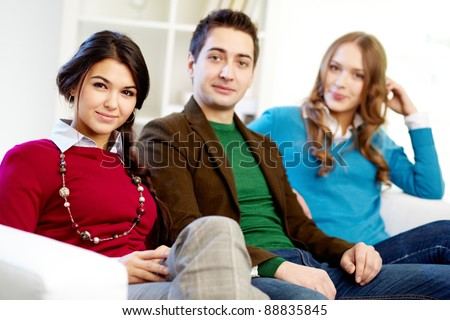 Portrait of attractive friends looking at camera while sitting on sofa - stock photo