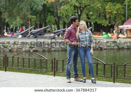 Portrait of attractive girl embracing her boyfriend outdoors.  - stock photo