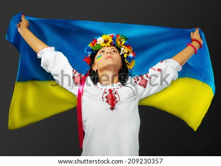 Portrait of attractive girl in national dress with a Ukrainian flag in her hands and with a Ukrainian flag on her face - stock photo