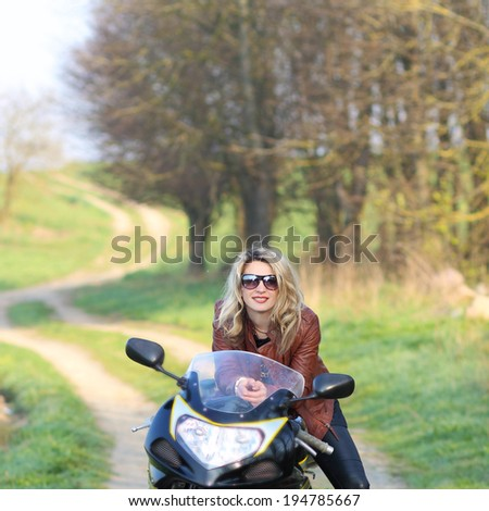 Portrait of attractive girl on sports bike. Biker girl with sunglasses and motorcycle - stock photo