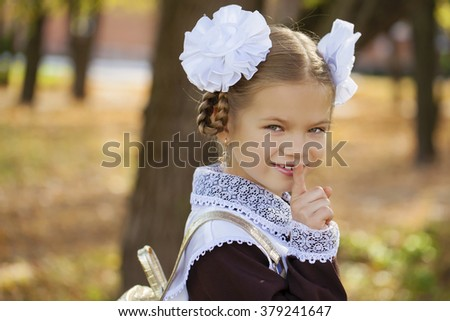 Portrait of attractive girl with finger on lips, concept of student show quiet, silence, secret gesture, young schoolgirl in a festive school uniform on the background autumn park - stock photo