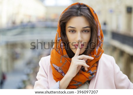 Portrait of attractive girl with finger on lips, concept of student show quiet, silence, secret gesture, young pretty brunette woman - stock photo