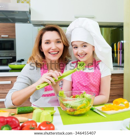 Portrait of attractive happy mother and daughter cooking a salad at the kitchen. - stock photo
