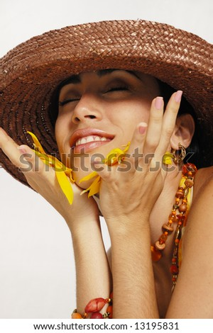 Portrait of attractive hispanic model holding sunflower petals - stock photo