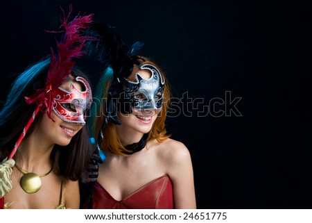 Portrait of attractive ladies holding carnival masks and looking through them - stock photo