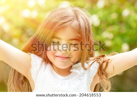 Portrait of attractive little Arabic girl with closed eyes enjoying sunny day, having fun outdoors, pleasure and happiness concept - stock photo