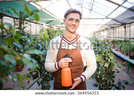 Portrait of attractive male gardener in glasses standing and holding water pulveriser in greenhouse - stock photo