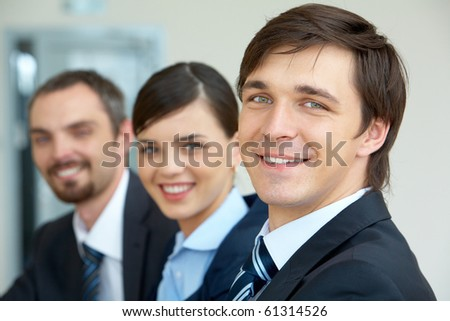 Portrait of attractive male looking at camera with his partners on background - stock photo