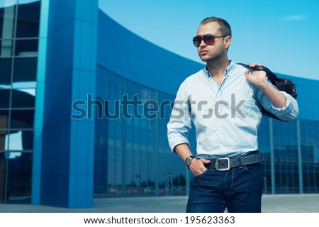 Portrait of attractive man in trendy casual clothing with leather bag and sunglasses posing over shopping mall. Sunny spring weather with blue sky. Outdoor shot - stock photo