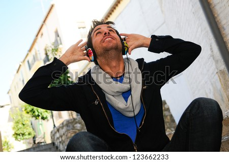 Portrait of attractive man in urban background listening to the music - stock photo