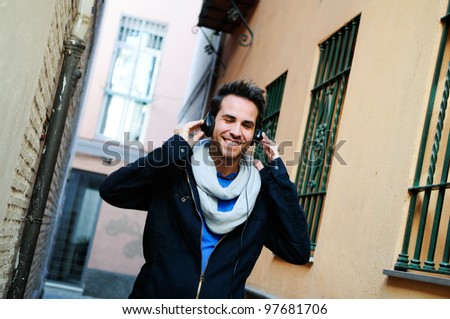 Portrait of attractive man in urban background listening to the music and dancing - stock photo