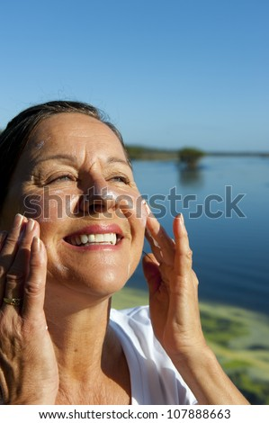 Portrait of attractive mature woman with suncream on her face to protect herself from skin cancer, isolated with blurred background and copy space. - stock photo