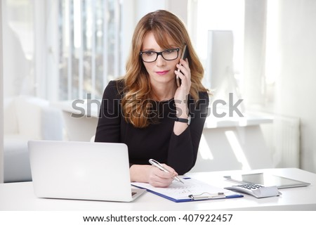 Portrait of attractive middle aged businesswoman sitting in front of laptop and making call while working on new on new project. - stock photo