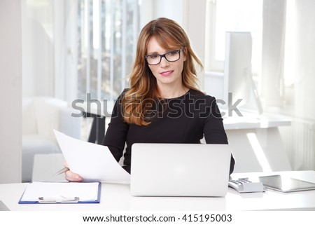 Portrait of attractive middle aged professional woman doing some paperwork while sitting at office in front of laptop and working on business plan. - stock photo