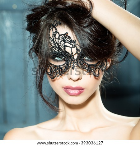 Portrait of attractive mysterious sexy young sensual woman with brunette hair in lace black mask looking forward with bare shoulders in studio on wooden background, square picture - stock photo