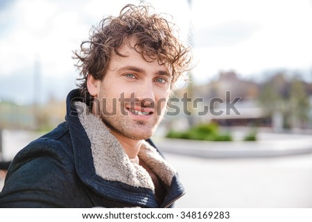 Portrait of attractive positive smiling happy curly young man in black jacket - stock photo