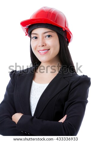 Portrait of attractive professional female contractor wearing red helmet. Cheerful asian businesswoman smiling and looking at camera. Isolated on white background. - stock photo