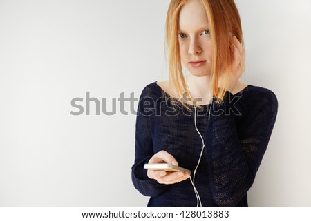 Portrait of attractive redhead female wearing earphones. Pretty Caucasian teenage girl with ginger hair wearing stylish black top, holding cell phone, listening to her favorite track on smart phone   - stock photo