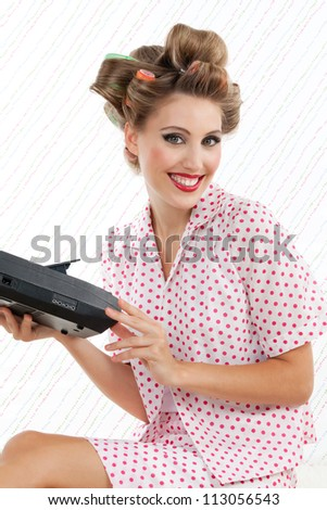 Portrait of attractive retro styled woman with cassette player - stock photo