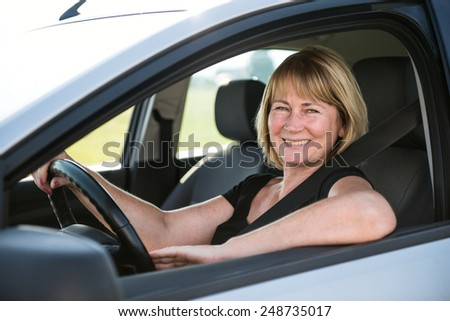 Portrait of attractive senior smiling woman sitting in car - stock photo