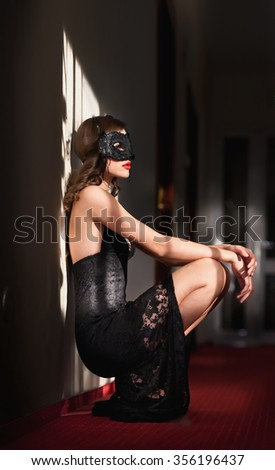 Portrait of attractive sensual young woman with mask, indoors. Sexy brunette lady posing provocatively sitting on the floor. Beautiful long hair girl with red lips and short lace dress, boudoir shot - stock photo