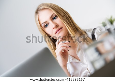 Portrait of attractive serios caucasian businesswoman with hand at chin at office desk with laptop and glass of water - stock photo