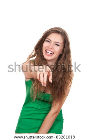 portrait of attractive smile laugh teenage girl, pointing her finger, wear green shirt, white teeth, brown long hair, isolated over white background concept of student point at you, young pretty woman - stock photo