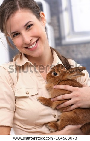 Portrait of attractive smiling girl cuddling with pet brown rabbit. - stock photo