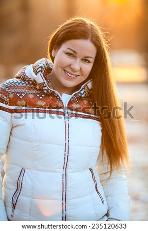 Portrait of attractive smiling woman in white down jacket in the sunlight - stock photo
