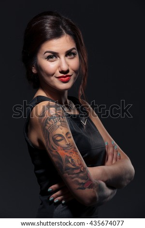 Portrait of attractive smiling young woman with tattoo on her hands - stock photo