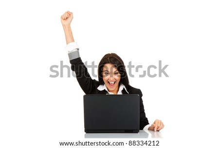 portrait of attractive surprised excited smile business woman sit at desk hold hand up looking at laptop screen, isolated over white background, Winner businesswoman with success - stock photo
