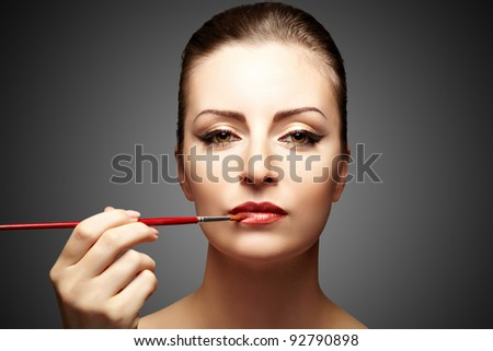 Portrait of attractive woman applying makeup on a dark background - stock photo