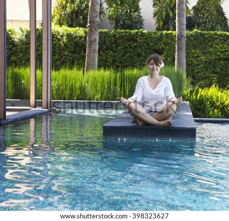 Portrait of attractive woman dressed in white sitting in meditating position by the pool - stock photo