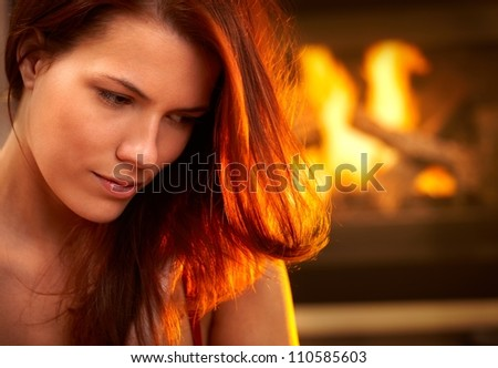 Portrait of attractive woman looking down, daydreaming in front of fireplace. - stock photo