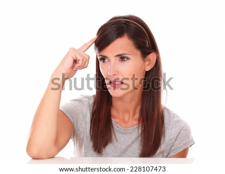 Portrait of attractive woman wondering with her hand on head while looking to her right on isolated white background - copyspace - stock photo