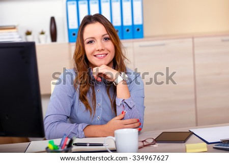 Portrait of attractive woman working in office, she siting at office desk. - stock photo