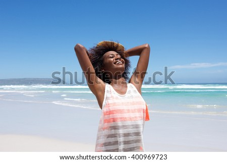 Portrait of attractive young african american woman enjoying a day at the beach   - stock photo