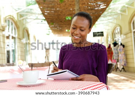 Portrait of attractive young african american woman sitting at coffee shop and writing notes  - stock photo