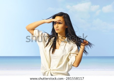 Portrait of attractive young Asian girl on the beach, shading eyes by hand. - stock photo