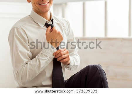 Portrait of attractive young blond businessman in white classical shirt and dark tie looking in camera, smiling and adjusting cufflink while sitting in room, close-up - stock photo