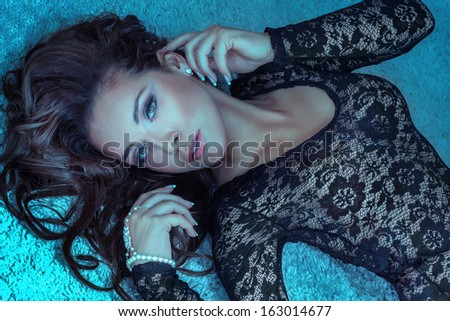 Portrait of attractive young brunette woman lying, looking at camera. Long curly hair. - stock photo