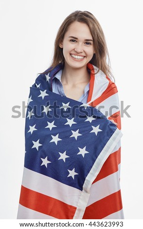 Portrait of attractive young brunette woman wrapped in National Flag celebrating Independence Day on 4th of July in United States of America.Cute model with toothy smile on isolated background - stock photo
