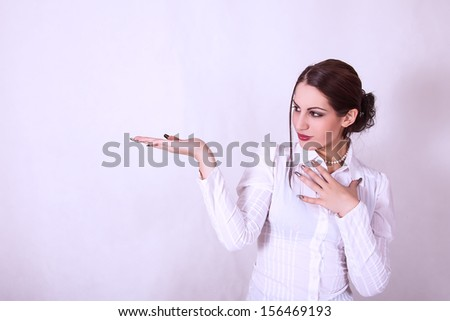 portrait of attractive young business woman showing something on a palm - stock photo