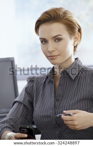 Portrait of attractive young businesswoman holding mobilephone, looking at camera. - stock photo