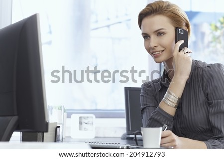 Portrait of attractive young businesswoman talking on mobilephone, using computer, sitting at desk. - stock photo