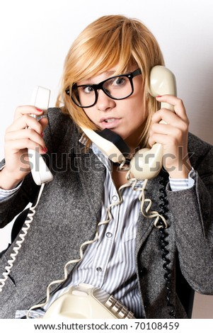 portrait of attractive young businesswoman with three phones - stock photo