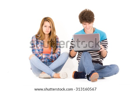 Portrait of attractive young couple in love man and woman isolated over white background sitting on floor, he looks to computer while she is mad. - stock photo